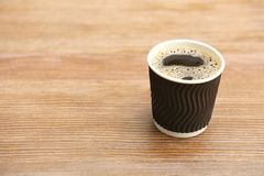 Cardboard cup of coffee on wooden table stock photography