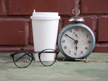 Cardboard cup hot coffee with old alarm clock and glasses Stock Photo