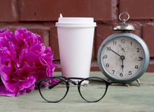 Cardboard cup with old alarm clock, glasses and peony Stock Photo