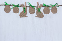 Cardboard Easter eggs and bunnies hanging on white background. Stock Image