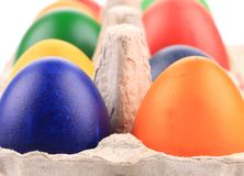 Cardboard egg box with colorful eggs. Stock Photo