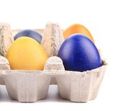 Cardboard egg box with Easter colored eggs Stock Photos