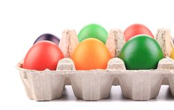 Cardboard egg box with Easter colored eggs Royalty Free Stock Photos