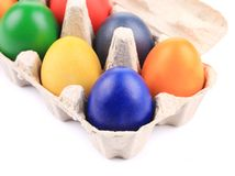 Cardboard egg box with Easter colored eggs. Royalty Free Stock Images