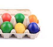 Cardboard egg box with Easter colored eggs. Royalty Free Stock Image