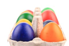 Cardboard egg box with Easter colored eggs Royalty Free Stock Photo