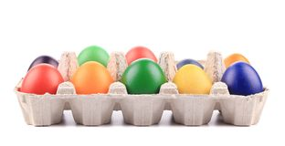 Cardboard egg box with Easter colored eggs. Stock Image