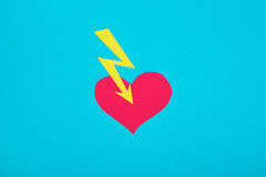 Cardboard figure of broken heart on a blue background. Royalty Free Stock Photos