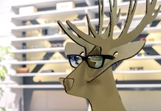 Cardboard figure of a deer in black sunglasses royalty free stock images