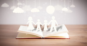 Cardboard figures of the family on opened book Royalty Free Stock Photo