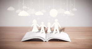 Cardboard figures of the family on opened book Royalty Free Stock Photos