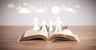 Cardboard figures of the family on opened book Stock Photography