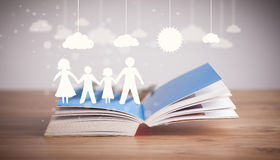 Cardboard figures of the family on opened book Stock Photo