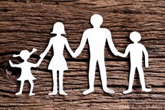 Cardboard figures of the family on a wooden table. Stock Images