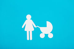 Cardboard figures of mom and child on a blue background. The sym Stock Image
