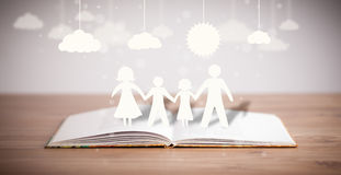 Cardboard Figures Of The Family On Opened Book Stock Images