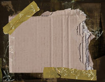 Cardboard on grunge background. Torn piece of cardboard taped to a grunge background with crumbled packing tape Stock Photo