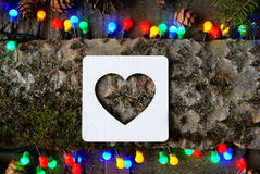 Cardboard heart icon and Christmas lights. On  wooden background Royalty Free Stock Images