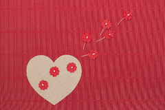 Cardboard heart with paper flowers on red corrugated background. Royalty Free Stock Photography