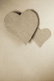Cardboard hearts. Two cardboard hearts over wrapping paper sheet stock image