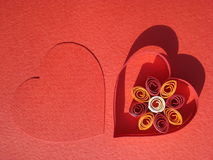 Cardboard hearts design. Cardboard hearts with copy space inside their border, on red background stock images