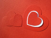 Cardboard hearts design. Red and white cardboard hearts with copy space inside their border, on red background royalty free stock image