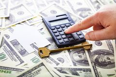 Woman counts on a calculator. Cardboard house,calculator and key on the money. Buying a property. Woman counts on a calculator Royalty Free Stock Image