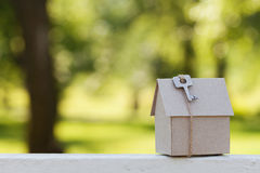 Cardboard house with key against green bokeh. Building, loan, housewarming, insurance, real estate or buying new home. Model of cardboard house with key against Royalty Free Stock Image