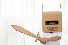 Cardboard knight. Portrait of playful child with cardboard helmet and sword Royalty Free Stock Photo