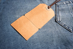 Cardboard label tied with leather to a blue jean, next to the back pocket. Stock Images