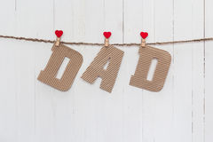 Cardboard letters DAD hanging on clothespins on a white wooden b Stock Image