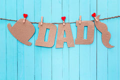 Cardboard letters DAD, hat and mustache hanging on clothespins o Royalty Free Stock Photos