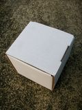 Cardboard mailing box on concrete floor. White cardboard mailing box on concrete floor Stock Image