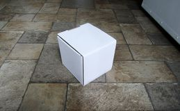 Cardboard mailing box on laminated floor. Cardboard mailing box lying on laminated floor at entrance Stock Photography
