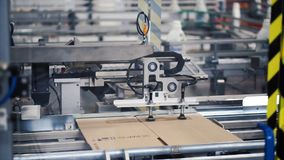 Cardboard package box packing machine. Clip. Box forming production line.  royalty free stock image