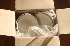 Cardboard Packing Box, Plates and Bubble Wrap Royalty Free Stock Photos