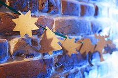 Cardboard paper rusty garland on red orange brick wall. Hearts, stars, twig tree, elk, deer. Yellow front lightning and blue back. Lightning royalty free stock image