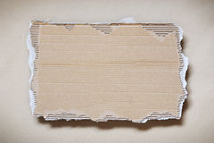 Cardboard Piece. A piece of ripped and rough cardboard over wrapping paper royalty free stock photo