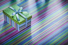 Cardboard present box with ribbon on striped tablecloth celebrat Stock Photography