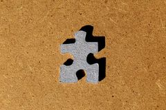 Cardboard puzzle piece on brown wooden background. Blue cardboard puzzle piece on brown wooden background royalty free stock photography