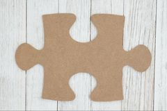 Cardboard puzzle piece on weathered whitewash textured wood background. You can use for a mockup stock photos