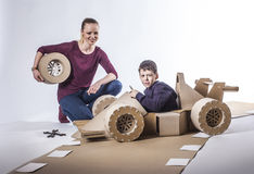 Cardboard racing car and happy family. Mother and son playing with a large cardboard racing car. happy family Royalty Free Stock Photography