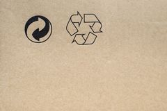 Cardboard with recycle symbols. Texture of a cardboard box with recycle symbols printed on it Royalty Free Stock Photos