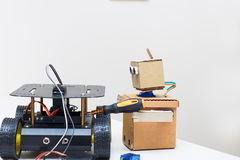 Cardboard robot holds a screwdriver and bot on the wheels. Cardboard robot holds a screwdriver and bot Stock Photos