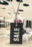 Sale sign hanging in clothes shop Royalty Free Stock Image