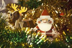 Cardboard Santa Claus and a Christmas deer in a New Year`s tinsel close up royalty free stock photo