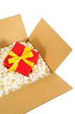 Cardboard shipping box, small red christmas gift inside, styrofoam polystyrene packing pieces Stock Images