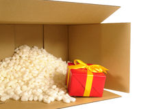 Cardboard shipping box, smallred gift inside, polystyrene packing nuts stock image