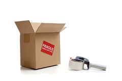Cardboard shipping box with a tape gun Royalty Free Stock Photo