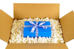 Cardboard shipping delivery box with blue gift inside and polystyrene packing pieces, top view Royalty Free Stock Photos